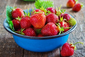fresh juicy organic strawberries in an old metal bowl