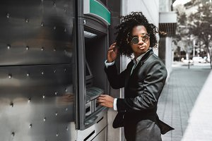 Businessman is using ATM outdoors