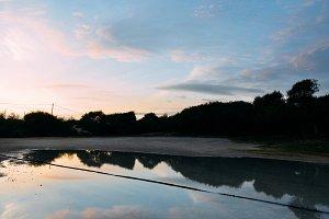 Reflection of sunset on puddle