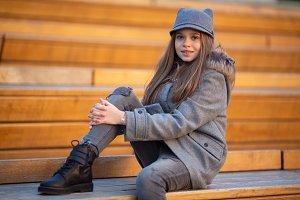 Photo of girl in gray coat sitting