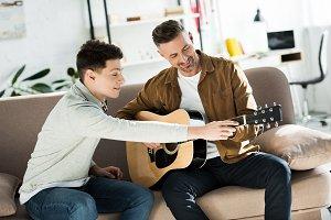 teen son teaching father play acoust