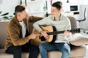 smiling teen son playing acoustic gu