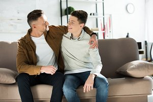 happy father and teen son hugging on