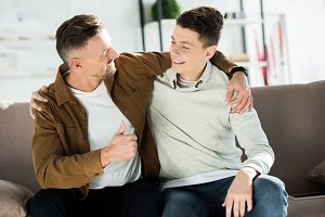smiling father and teen son hugging