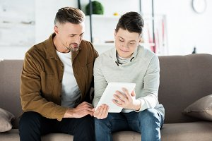 father and teen son using tablet and