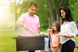 dad grilling at picnic with family