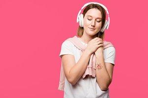 joyful young woman in headphones lis