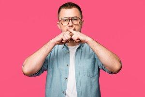 young man in eyeglasses gesturing fo