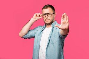 serious man adjusting eyeglasses and