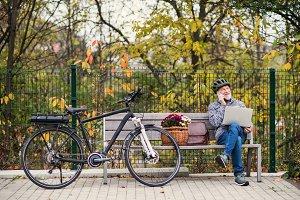 Senior man with electrobike sitting