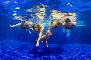 Happy family diving in swimming pool
