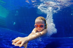 Funny child dive in swimming pool