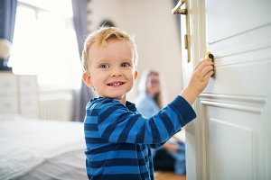 A toddler boy standing by the door