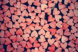 Tiny red hearts on dark background.