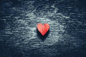Red heart on dark wooden background