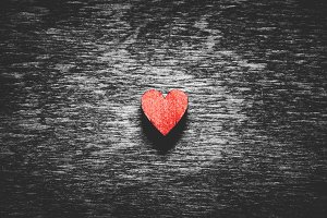 Red heart on black wooden background