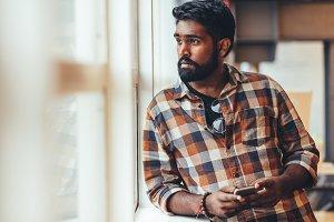 Man standing near a window looking