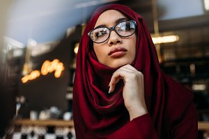 Woman in hijab looking away thinking