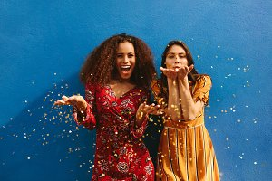 Female friends blowing off glitter
