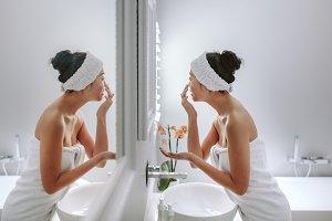 Woman in bathroom applying cosmetic
