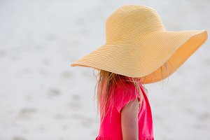 Adorable little girl in hat at beach