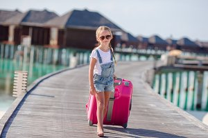 Little adorable girl with big luggag