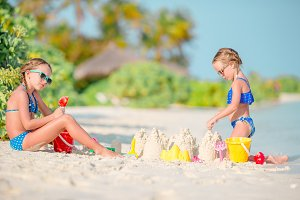 Two kids making sand castle and havi