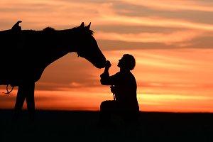 Rider pats horse at beautiful sunset