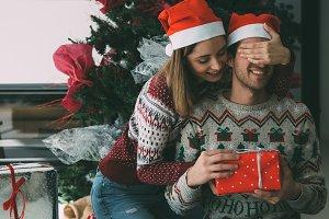 Young woman giving Christmas gift to