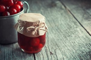 Jar of sour cherry jam and cherries.