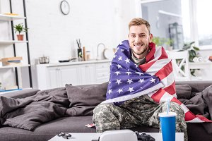smiling army soldier covered in amer