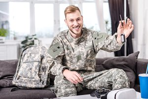 excited army soldier sitting on couc