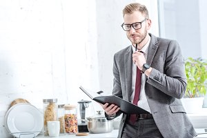pensive businessman holding notebook