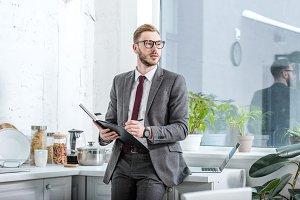 handsome businessman holding noteboo