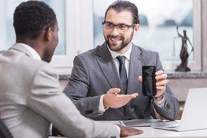 smiling businessman showing smartpho