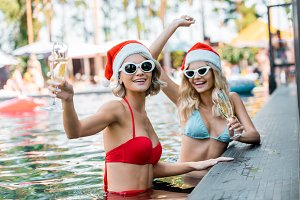 happy women in santa claus hats and
