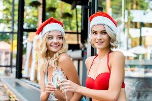 happy women in santa claus hats clin