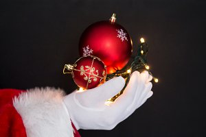 hands of santa claus holding lights