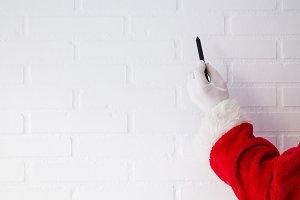 santa claus with pen on white brick