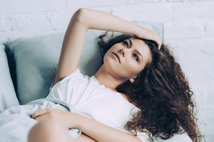 pensive young woman laying in bed du