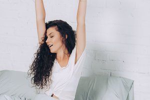 joyful young woman stretching in bed