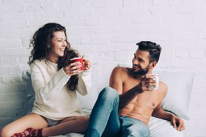 laughing young couple with cups of c