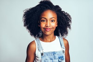 Cute young African girl in dungarees