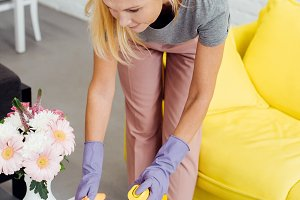mature woman in gloves cleaning tabl