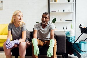 tired couple in rubber gloves sittin