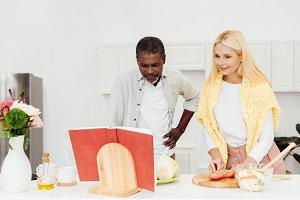 happy interracial couple cooking din