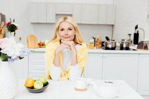 smiling woman sitting at kitchen and