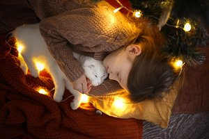 girl hugs and kisses cat near tree