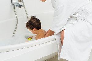 Mother in bathrobe washing son in ba