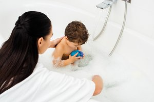 Woman washing toddler boy in white m